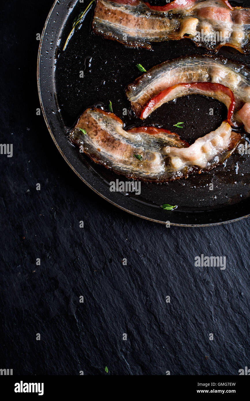 Pan of fried bacon on black slate background - Stock Image