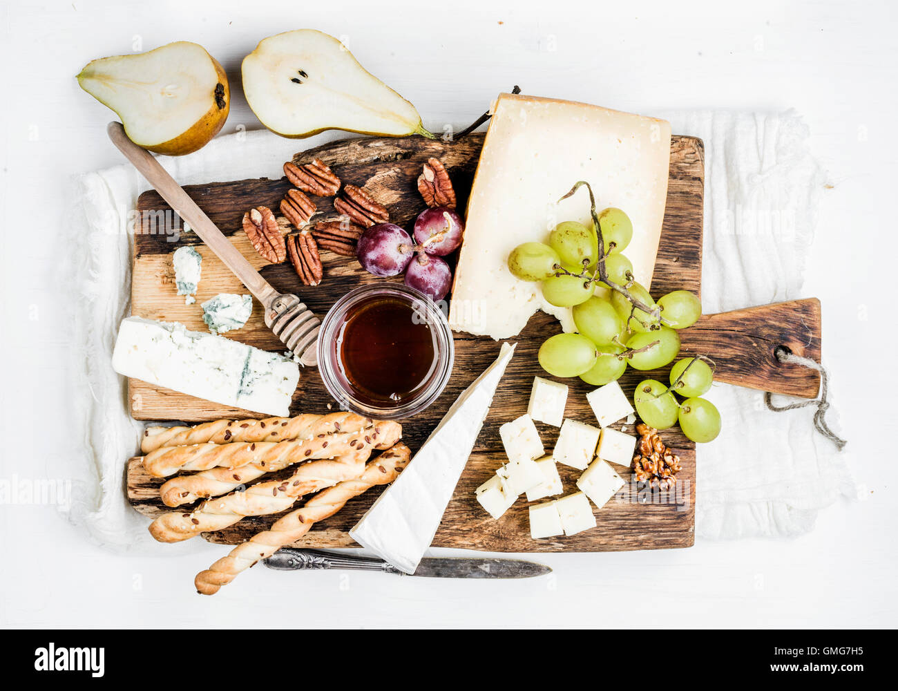 Cheese appetizer set. Various types of cheese, honey, grapes, pear, nuts and bread grissini sticks on rustic wooden - Stock Image