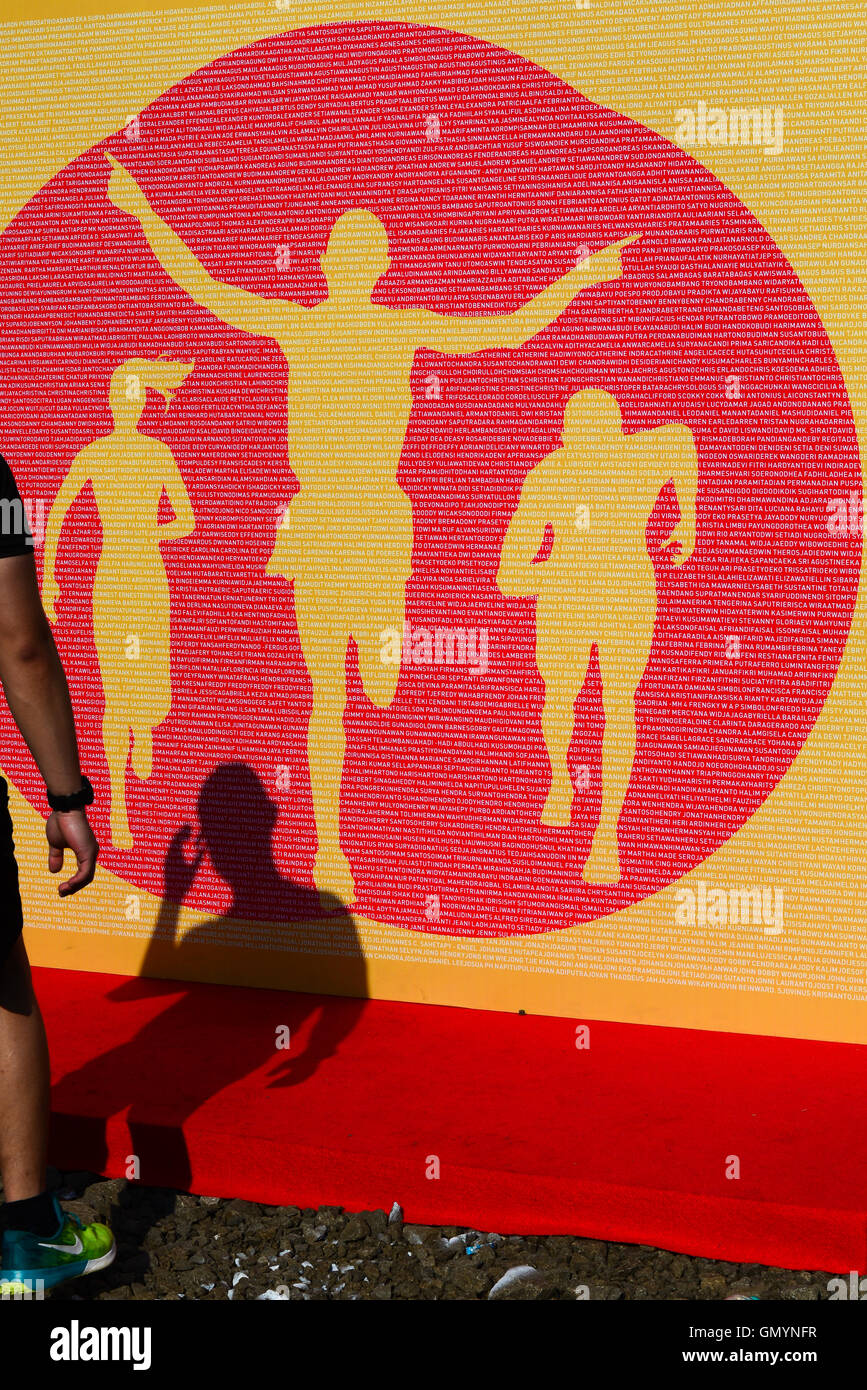 Shadow of a man and giant backdrop illustrating runners in a running event. © Reynold Sumayku - Stock Image