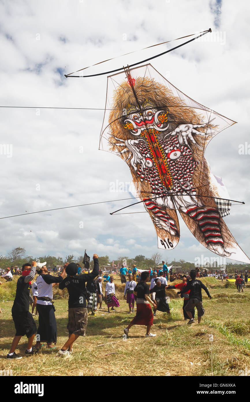 Sanur, Bali Island, Indonesia - July 15, 2012: Balinese men launch a big kite with the image of Rangda - mythic - Stock Image
