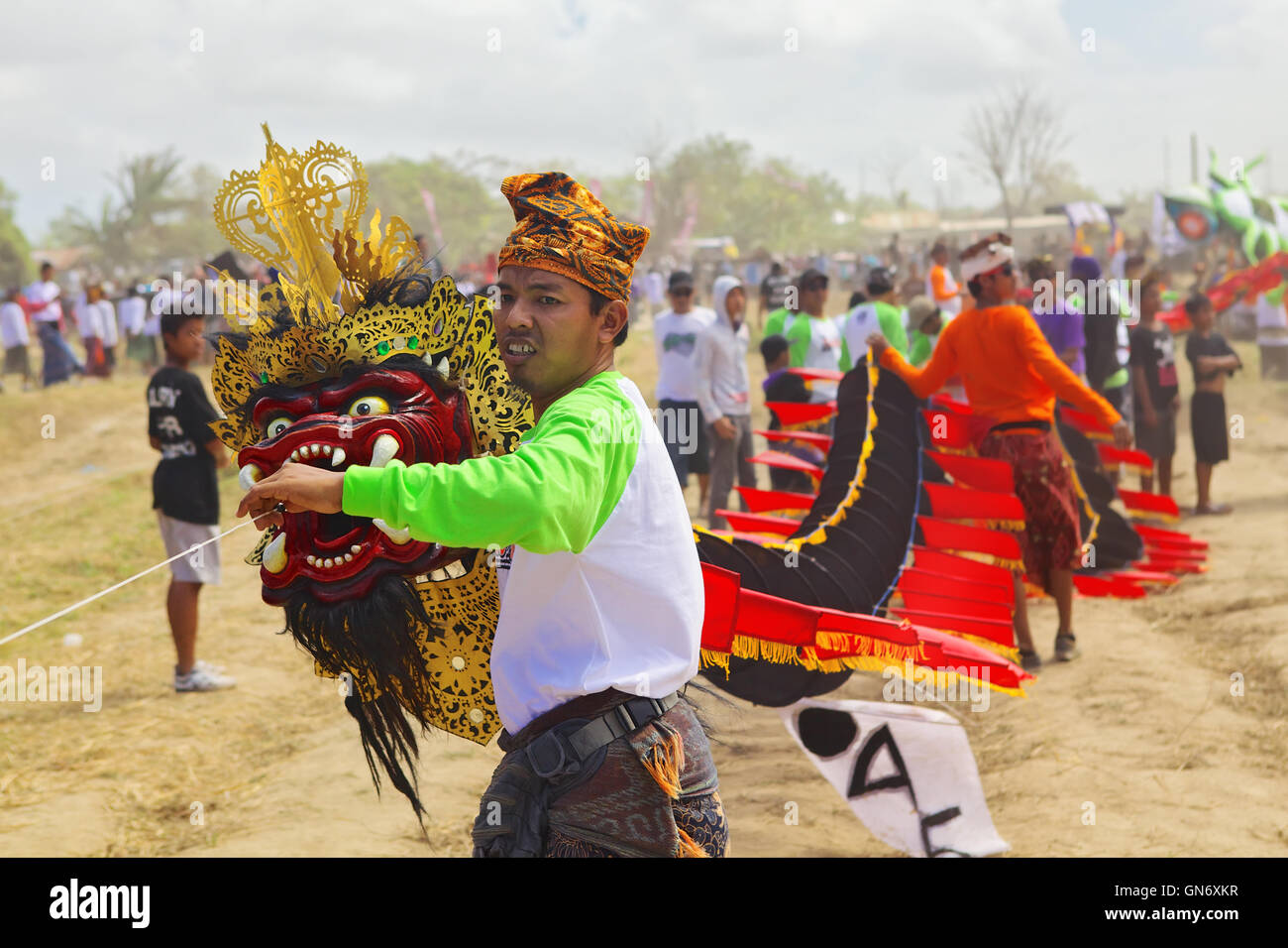Sanur, Bali Island, Indonesia -July 15, 2012: Balinese man launching kite with head of mythic dragon and long tail. - Stock Image