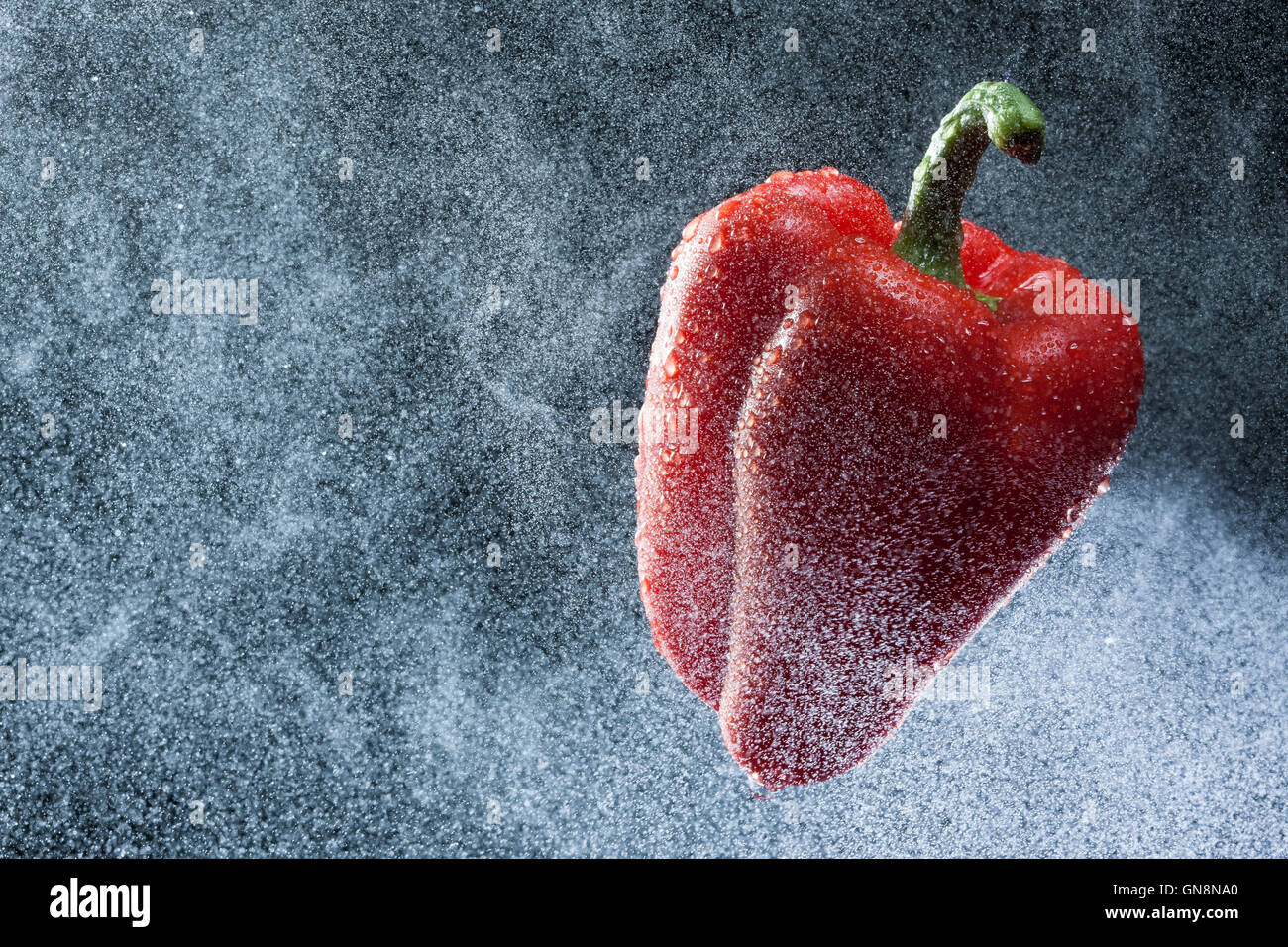 Red pepper in a spray against a black background. A series of fruits and vegetables in motion. - Stock Image
