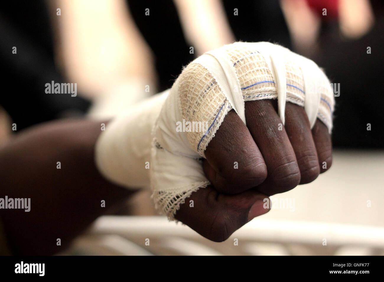 Kampala, Uganda. Aug. 31, 2016. Ugandan boxing coaches attentively following how to tie an Olympic boxing bandage - Stock Image