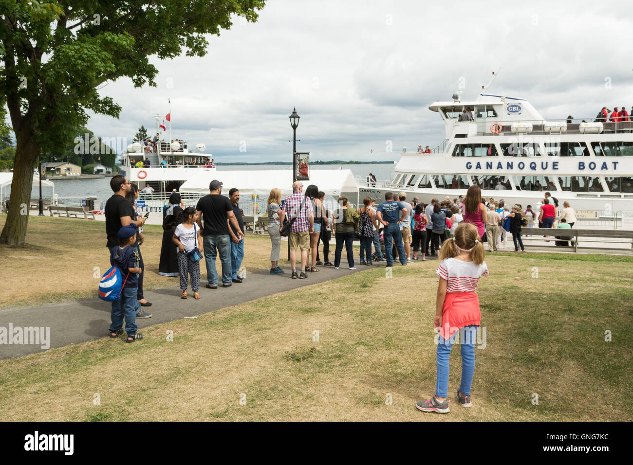 Gananoque, Ontario, Canada - tourists queuing for Thousand Islands Cruise boats on St Lawrence River by Gananoque - Stock Image