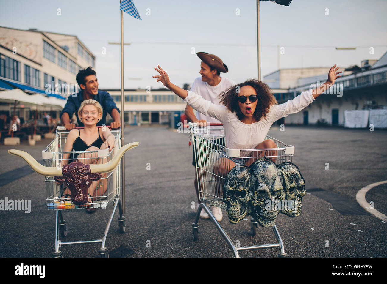 Young friends having fun on a shopping trolley. Multiethnic young people racing on shopping cart. - Stock Image