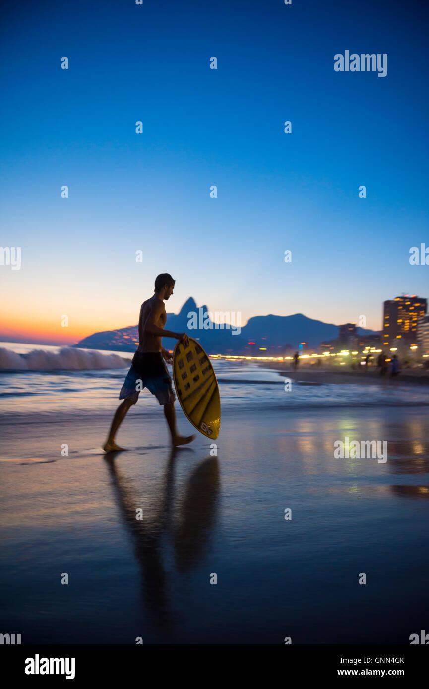 RIO DE JANEIRO - MARCH 24, 2016: Young carioca Brazilian skimboarder surveys the sunset waves on the shore of Ipanema - Stock Image