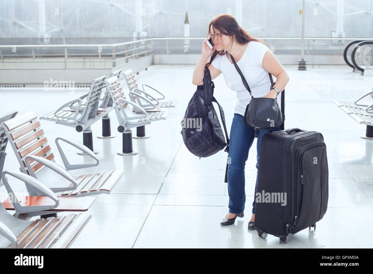 stressed troubled woman in the airport with plenty of bags and luggageStock Photo