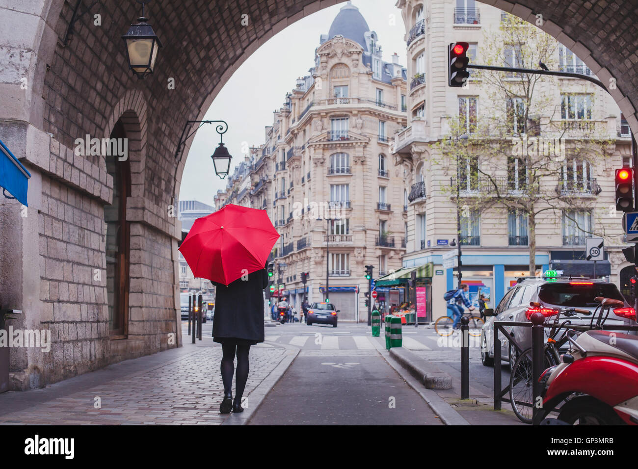 woman with red umbrella walking on the street of Paris, France Stock Photo