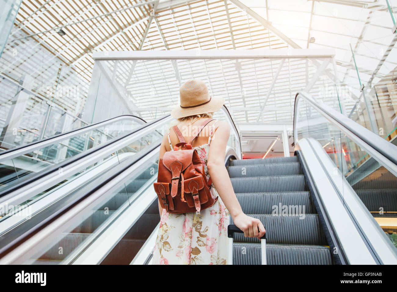 woman in modern airport, people traveling with luggage - Stock Image