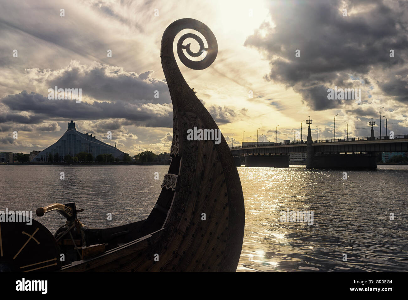 Nose Viking boat on the River Daugava on the background of the Latvian National Library and the Stone Bridge - Stock Image
