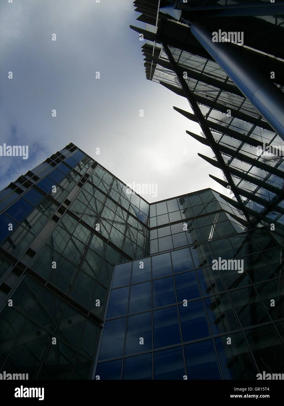Looking up at a number of glass buildings with a grey sky - Stock Image