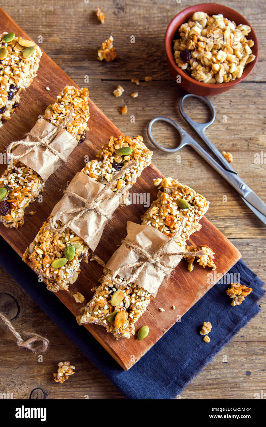 Organic homemade granola bars on rustic wooden background - Healthy vegetarian snack