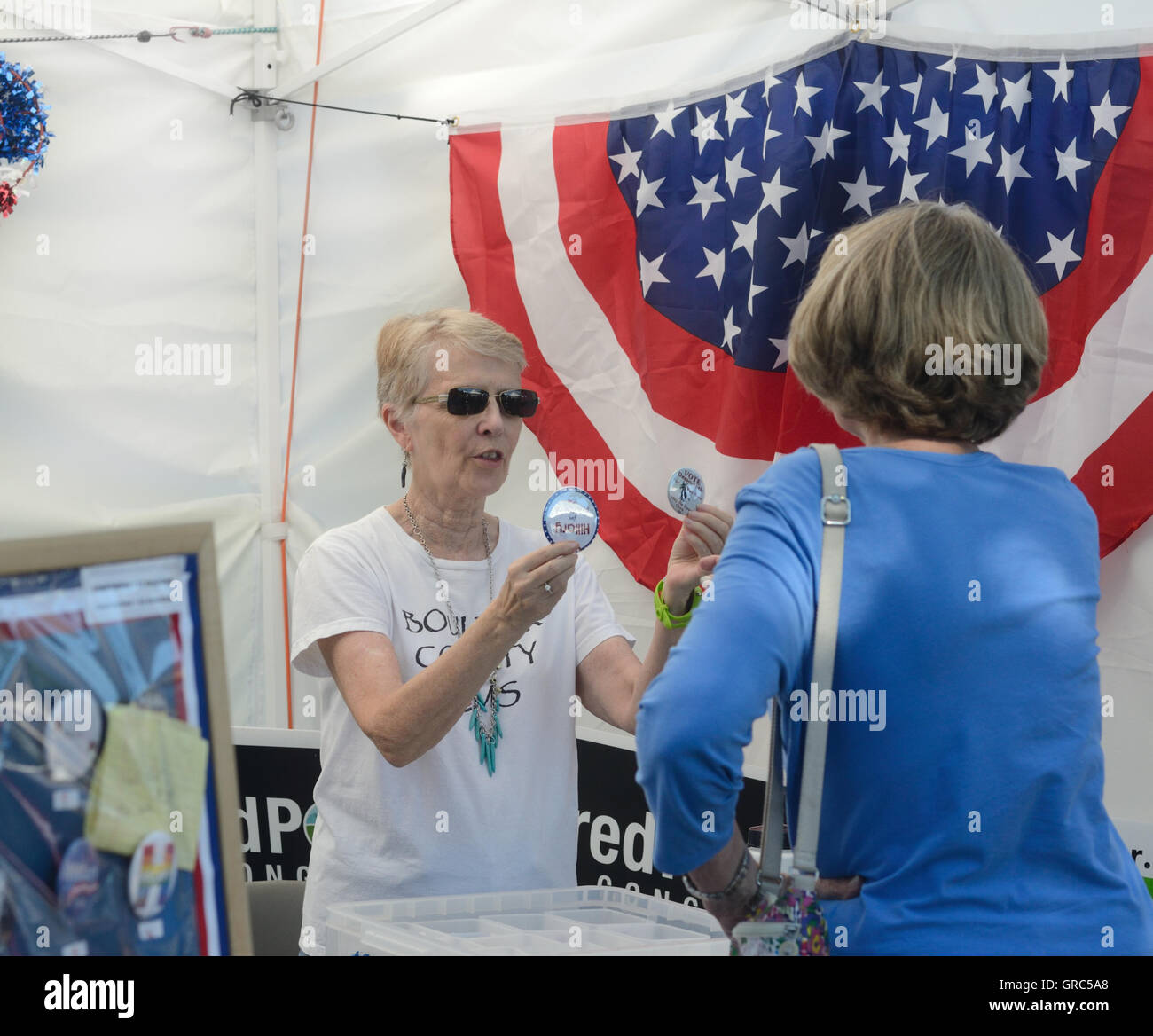 Donna Oleston shows festival-goer Democratic Party election buttons for sale at Boulder's Hometown Festival - Stock Image