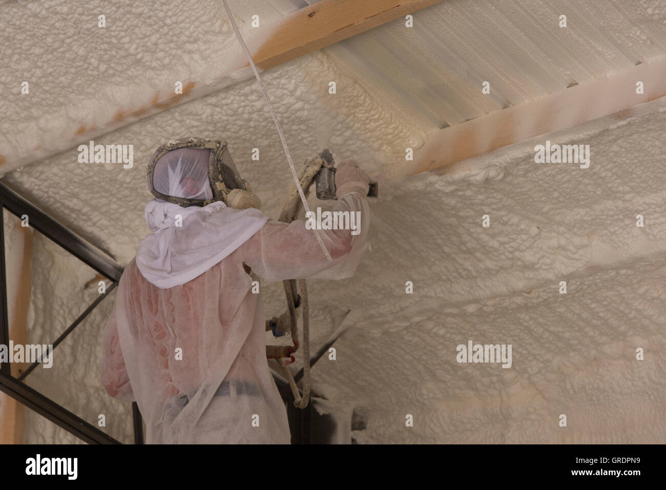 A technician applies open cell foam insulation to a structure's interior for sound control and energy conservation. - Stock Image