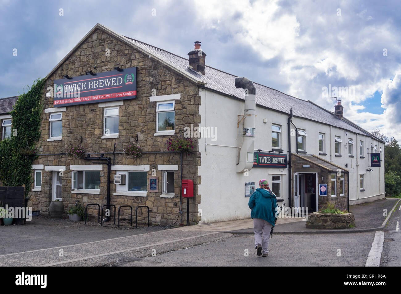 A walker arriving at the Twice Brewed Inn, Once Brewed, Cumbria, England Stock Photo