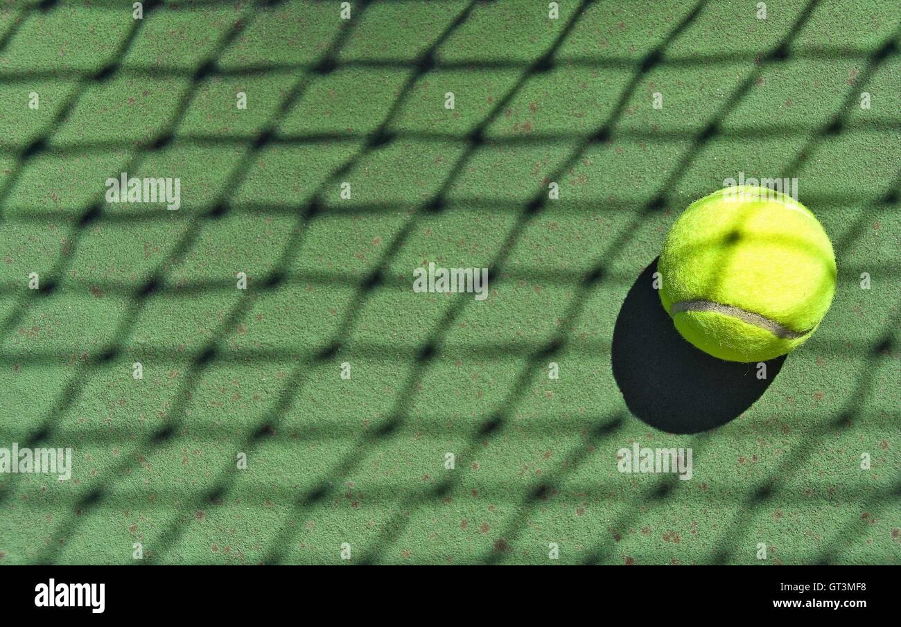 Crisscross net shadow on neon tennis ball. - Stock Image