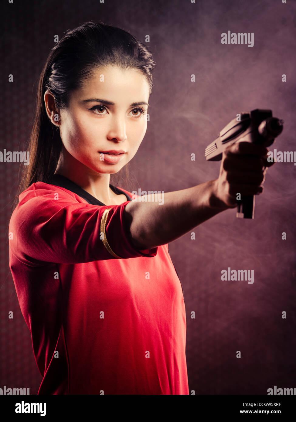 Beautiful trekkie wearing Star Trek original series 1967 red shirt uniform with original phaser - Stock Image