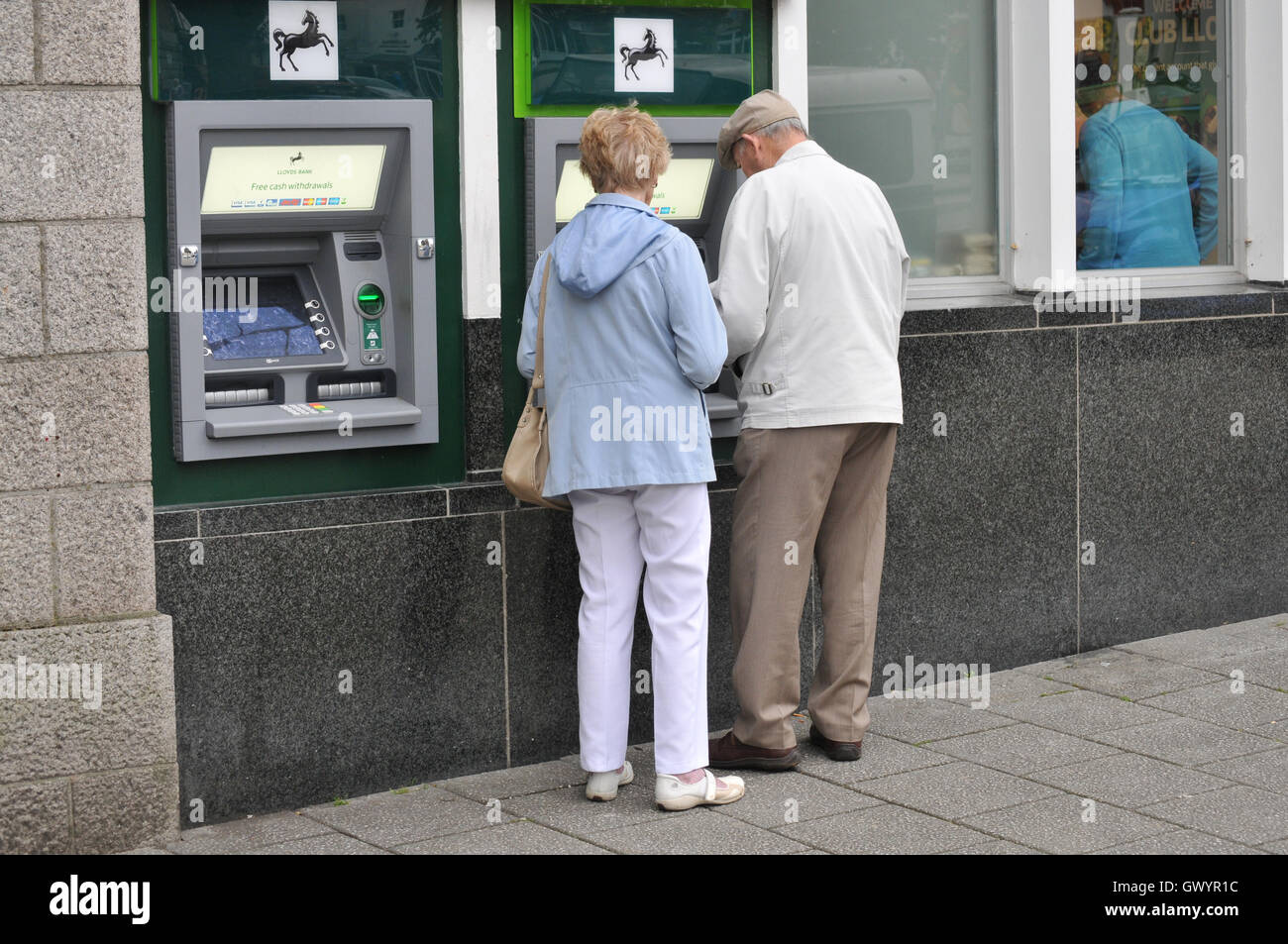 Two pensioners at a cash machine in Falmouth, Cornwall Stock Photo