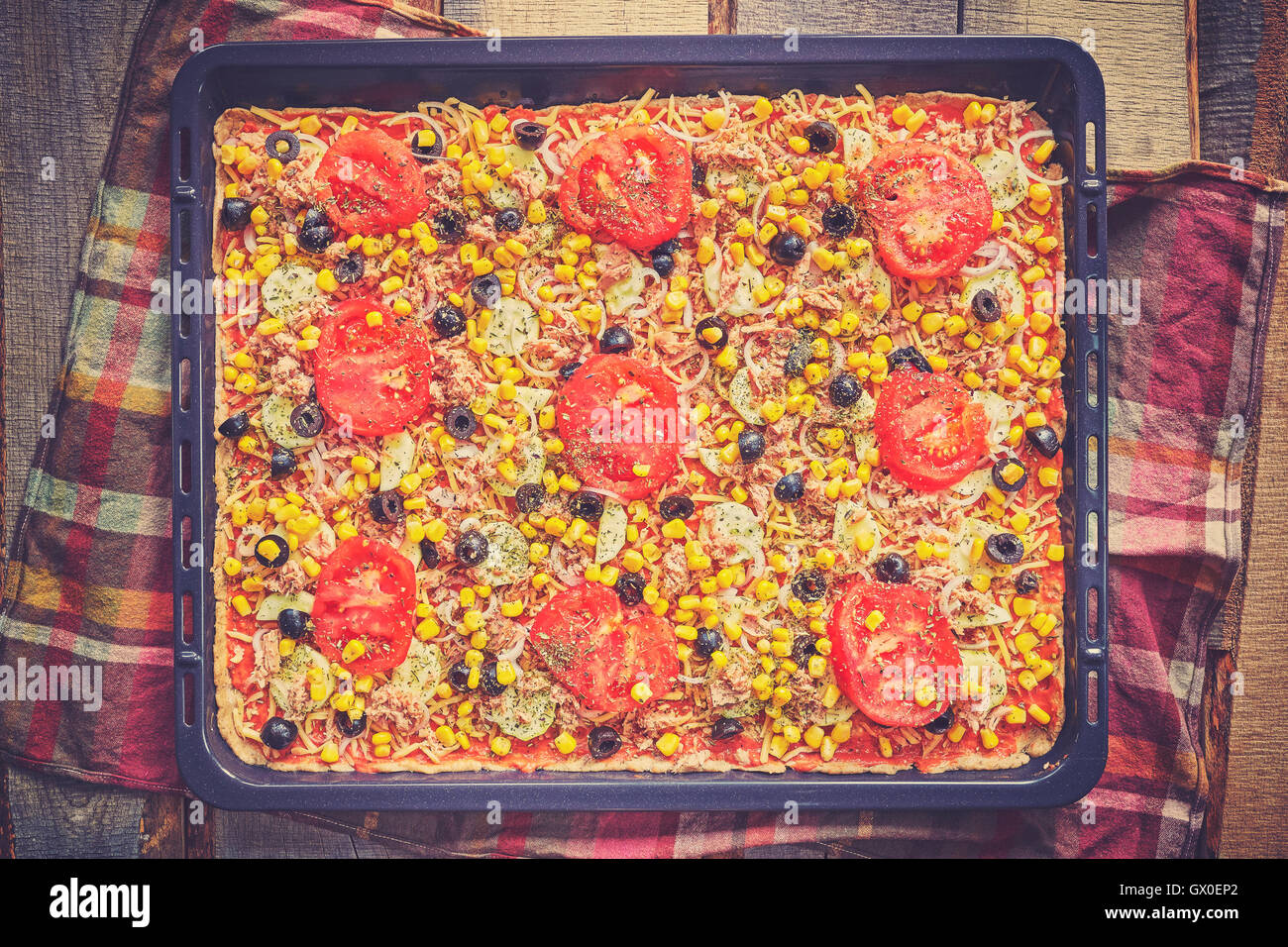 Vintage toned homemade tuna pizza with tomatoes, olives, onion and corn ready to bake on wooden background, top - Stock Image
