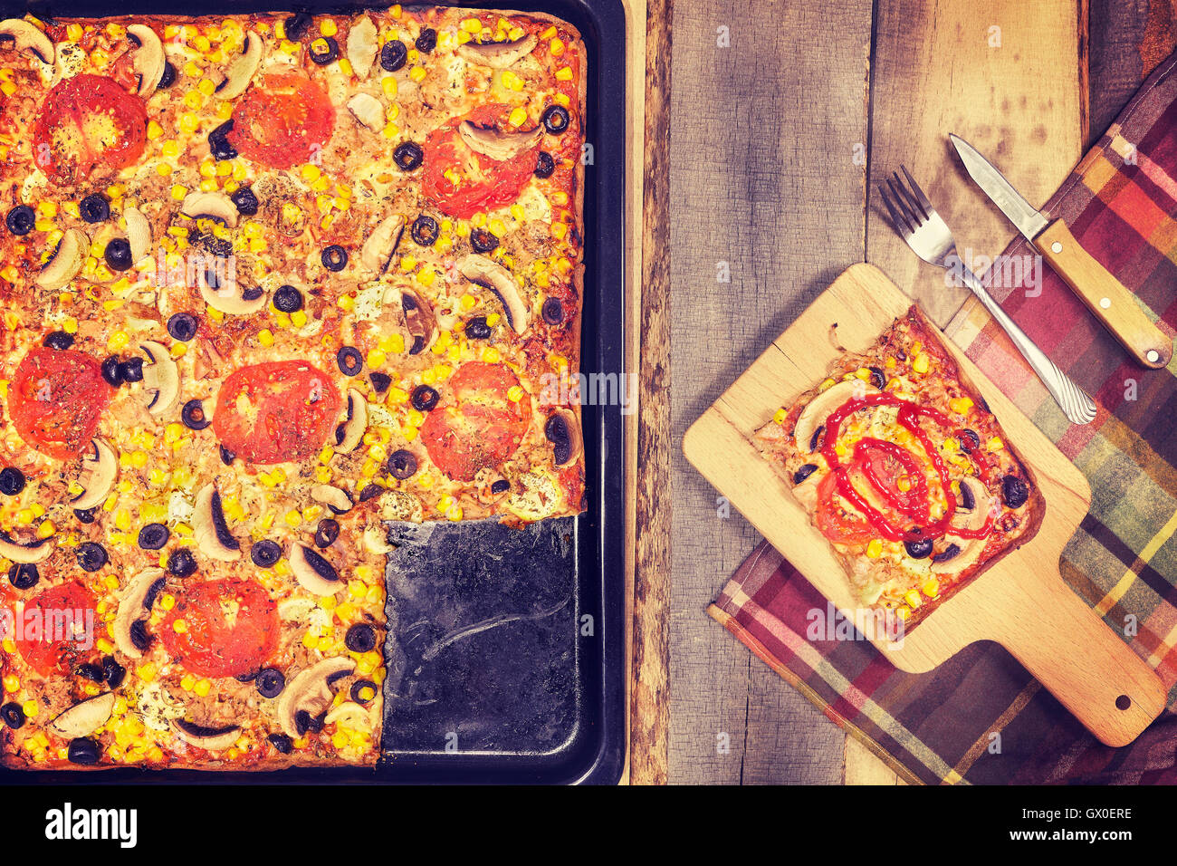 Vintage toned homemade tuna pizza with tomatoes, olives, onion and corn on wooden background, top view. - Stock Image