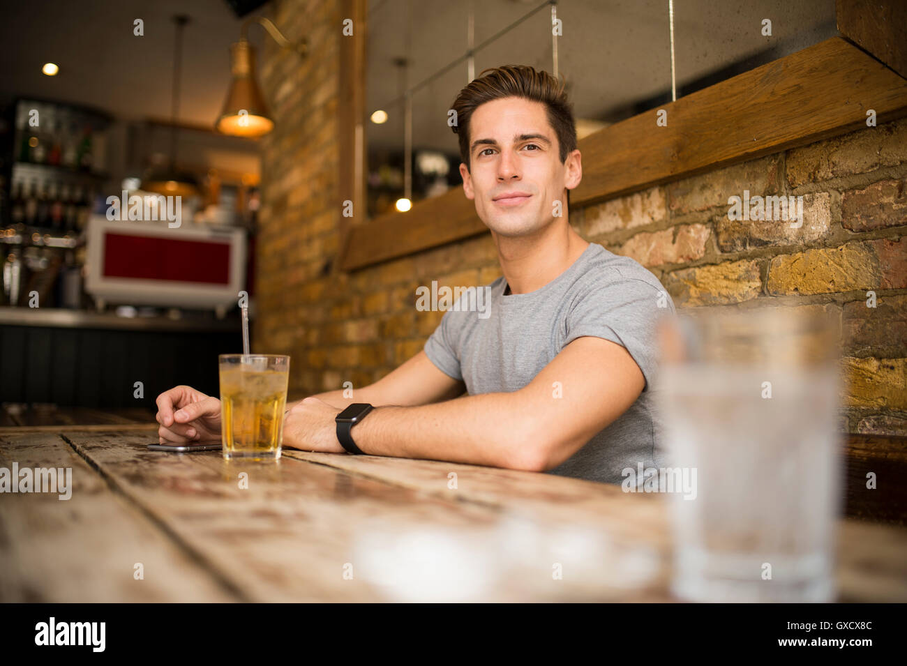 Young man at table in city bar - Stock Image
