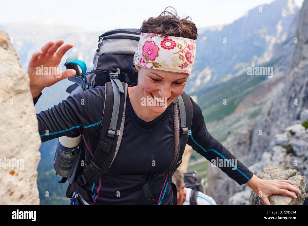 Woman hiking up mountain smiling, Austria - Stock Image