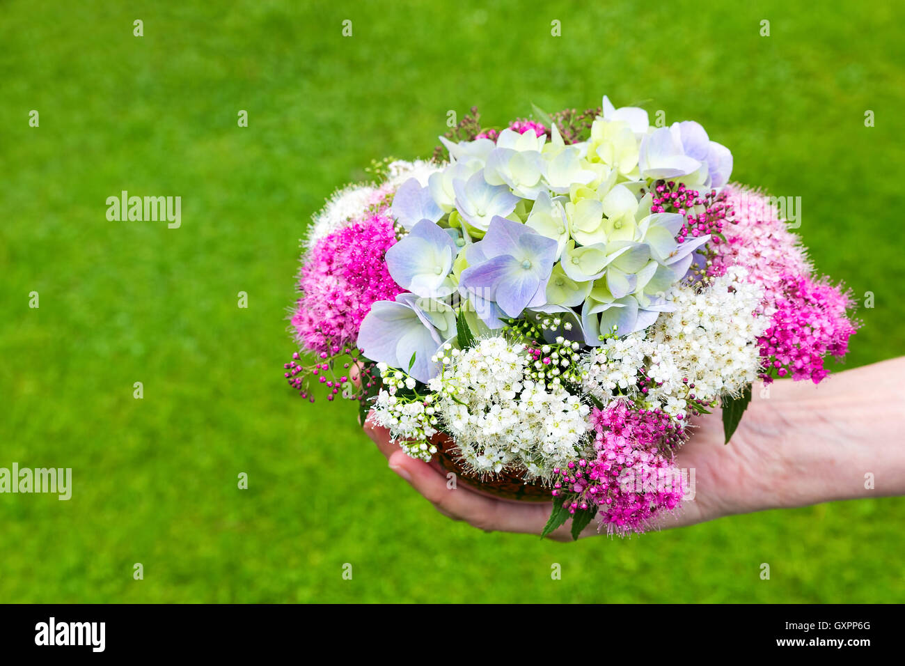 Hand giving bouquet of summer flowers on vase with grass background ...