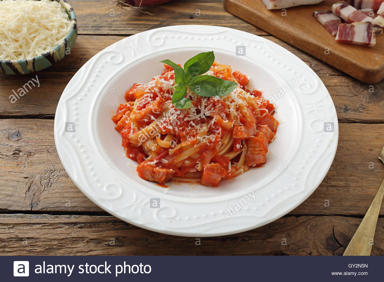 top view,pasta amatriciana, noodles in sauce tomato, ceramic plate on rustic chicken table background - Stock Image