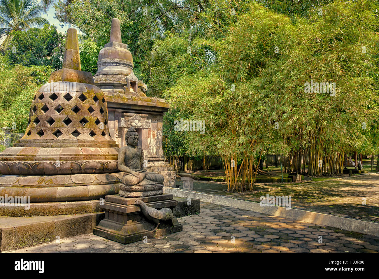 Buddha meditating in front of stone stupas in Mendut temple, Indonesia - Stock Image