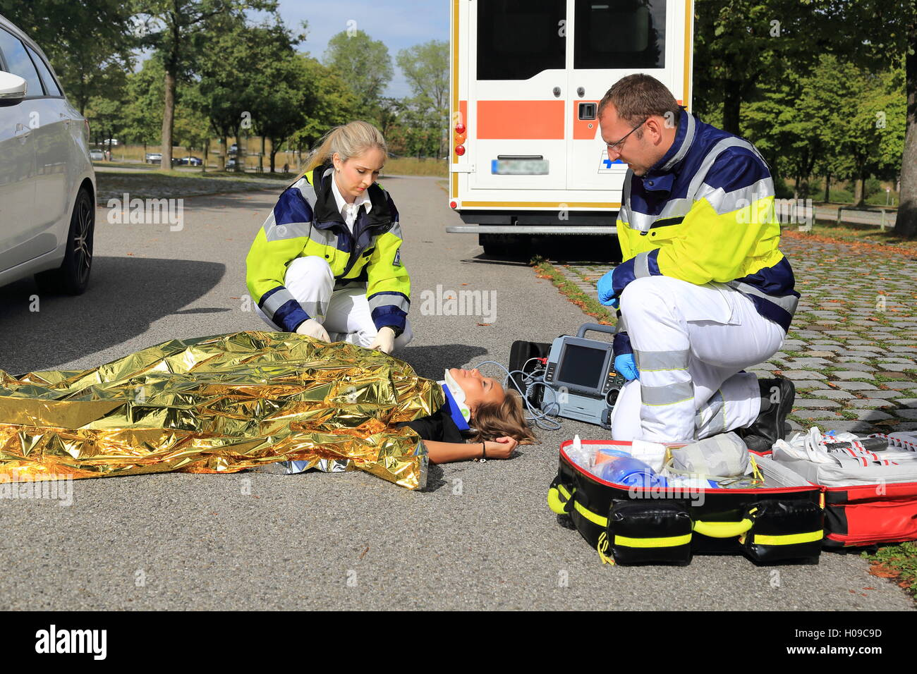 Two paramedics helping a woman after a traffic accident - Stock Image