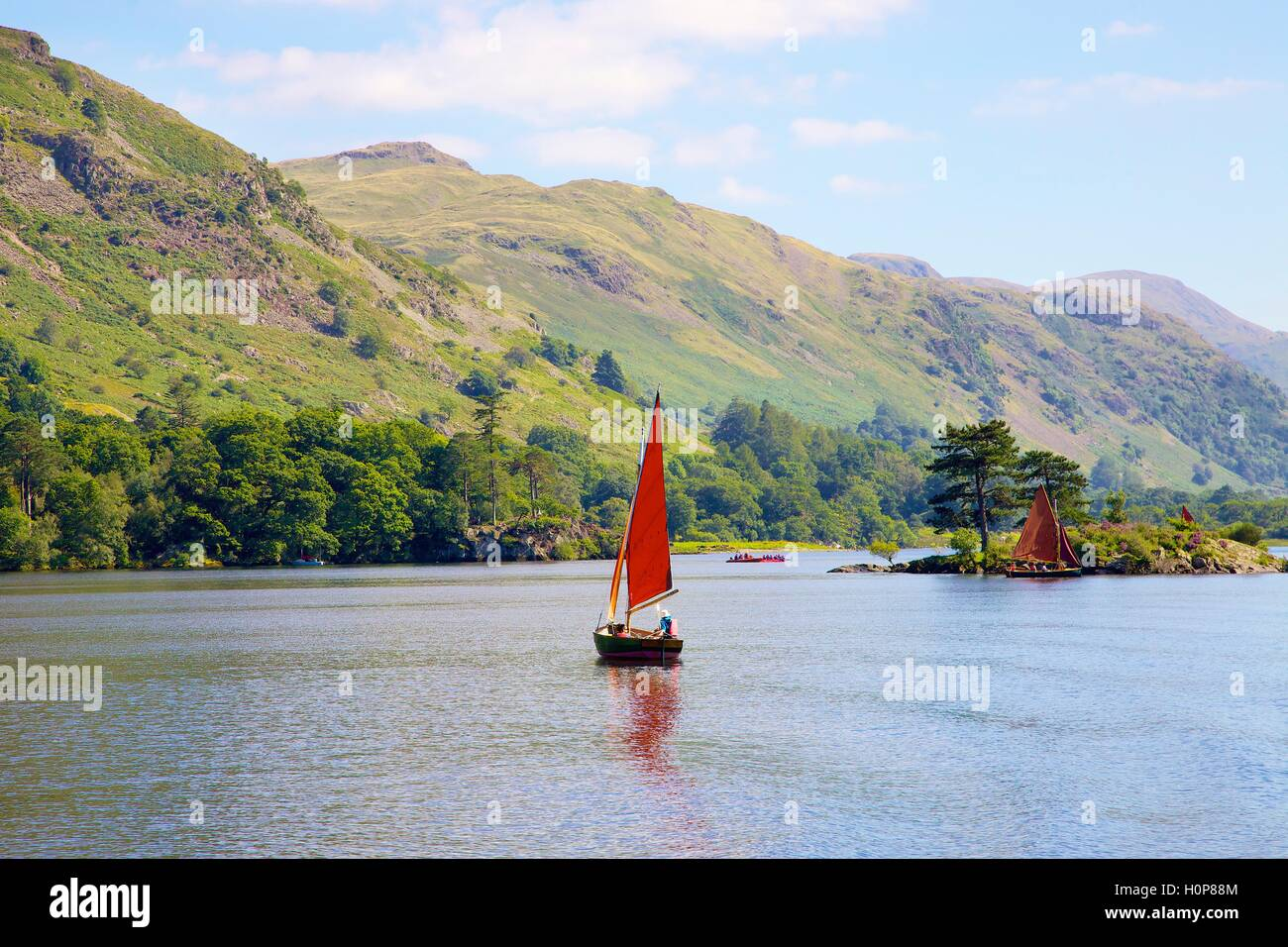 Red sailed boat sailing near Wall Holm island. Ullswater, Penrith, The Lake District National Park, Cumbria, England, Stock Photo