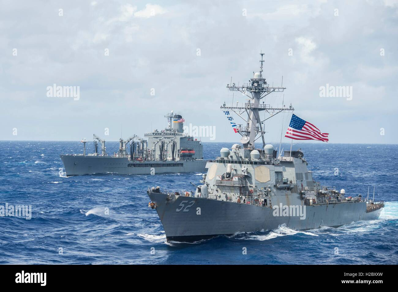 The USN Forrest Sherman-class guided-missile destroyer USS Barry (right) and the Henry J. Kaiser-class fleet replenishment - Stock Image