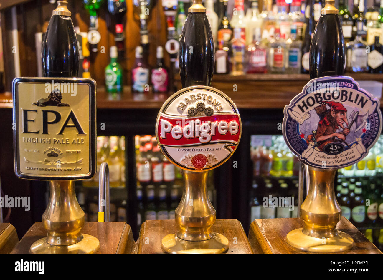 Pump clips for Marston's Pedigree, EPA and Wychwood Hobgoblin on a bar, Queen's Head pub, Hedon, East Riding, Yorkshire, Stock Photo