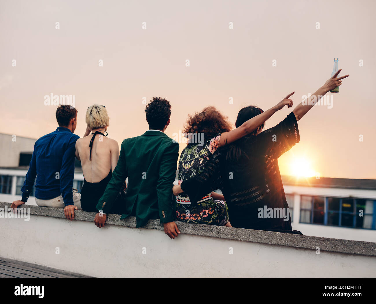 Group of friends partying on terrace with drinks. Young men and women enjoying drinks on rooftop at sunset. - Stock Image