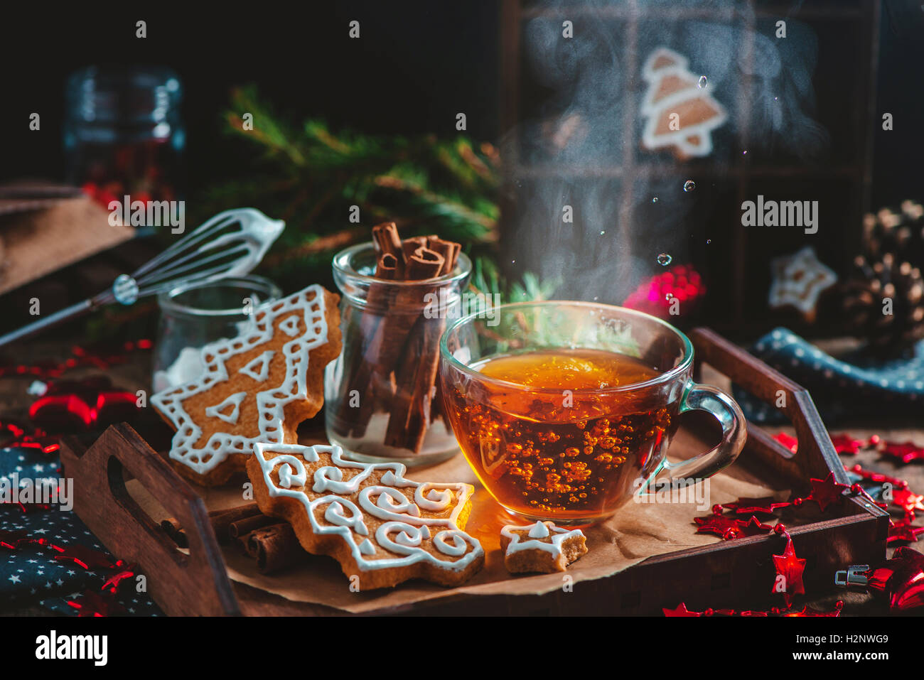 Christmas cookies with steaming cup of tea - Stock Image
