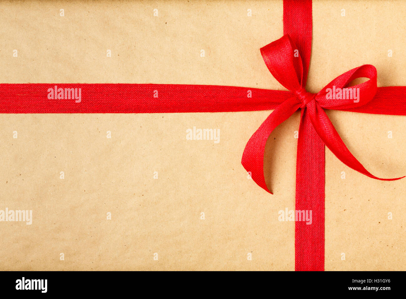 simple christmas gift christmas present background with recycled wrapping paper and red bow