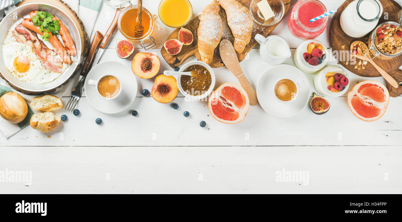Breakfast snacks and drinks set on white wooden background - Stock Image
