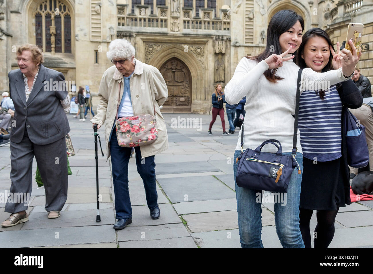 Two women tourists are pictured using a camera phone to take a selfie in front of Bath Abbey,England,UK Stock Photo