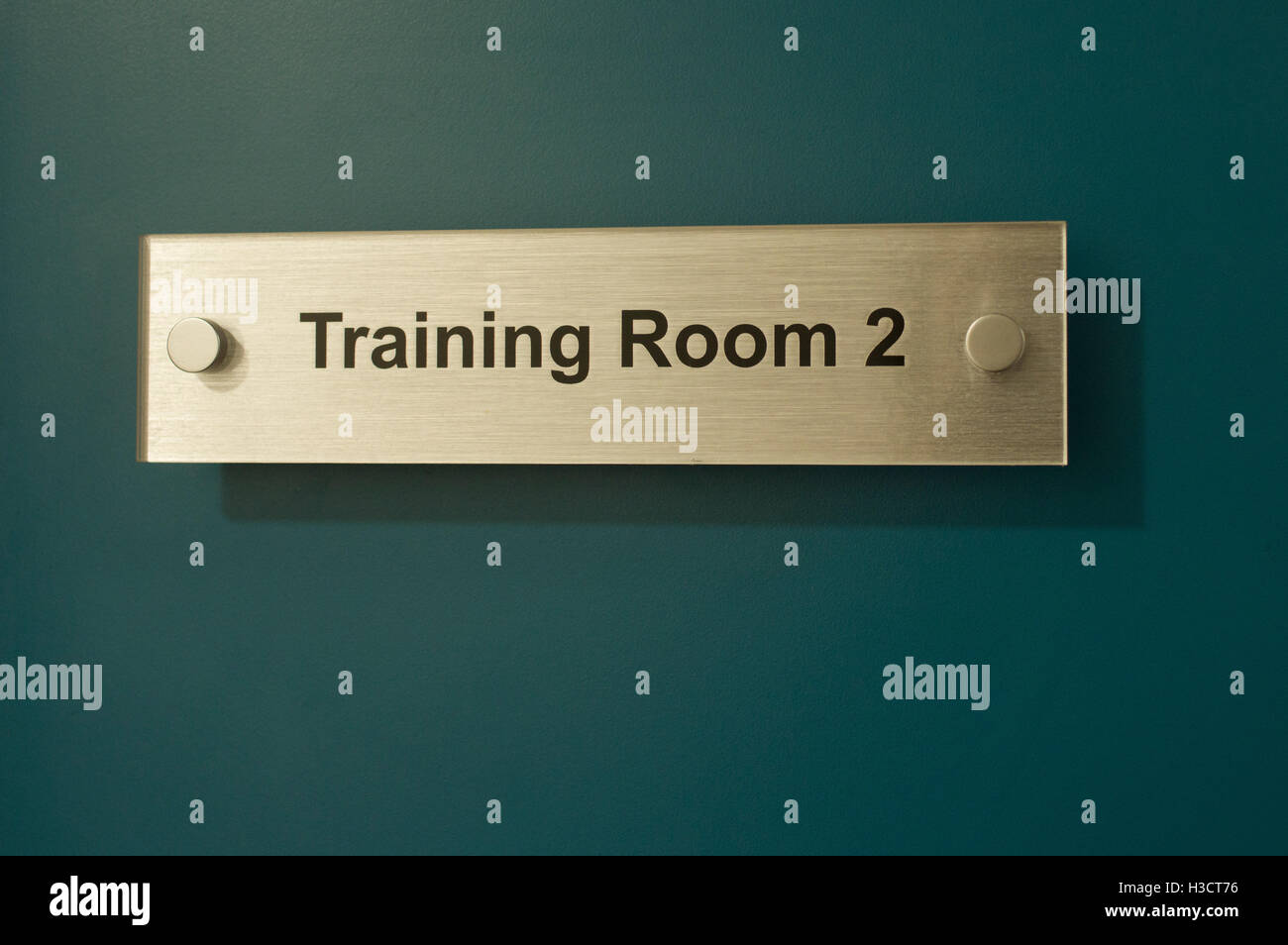 gold training room sign on a green door or wall stock photo