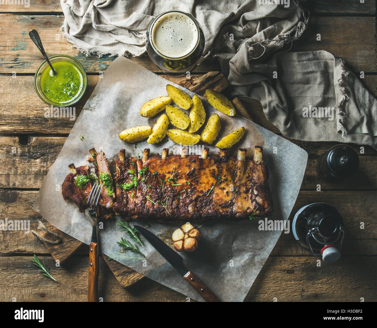 Roasted pork ribs with sauce, fried potato and dark beer - Stock Image