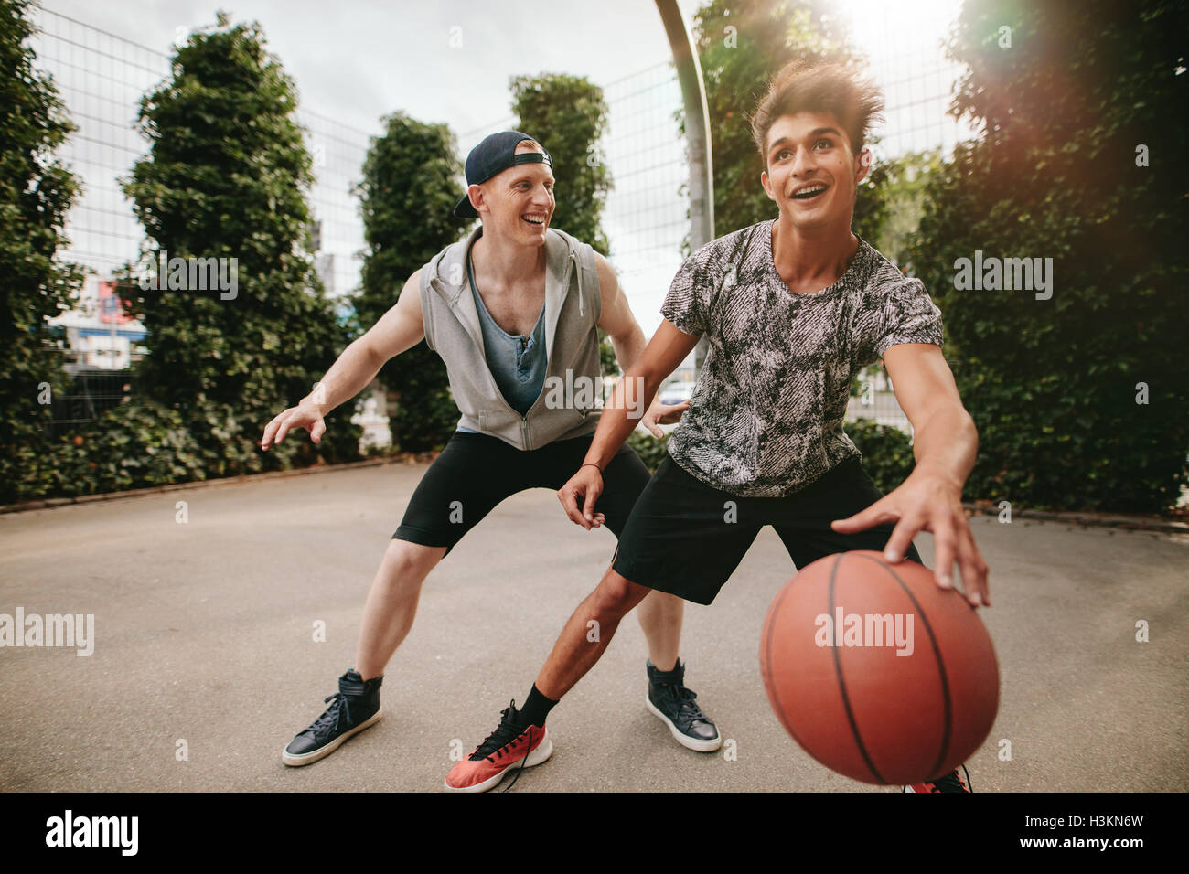 Two young friends playing basketball and having fun. Streetball players having a game of basketball on court outdoors. - Stock Image