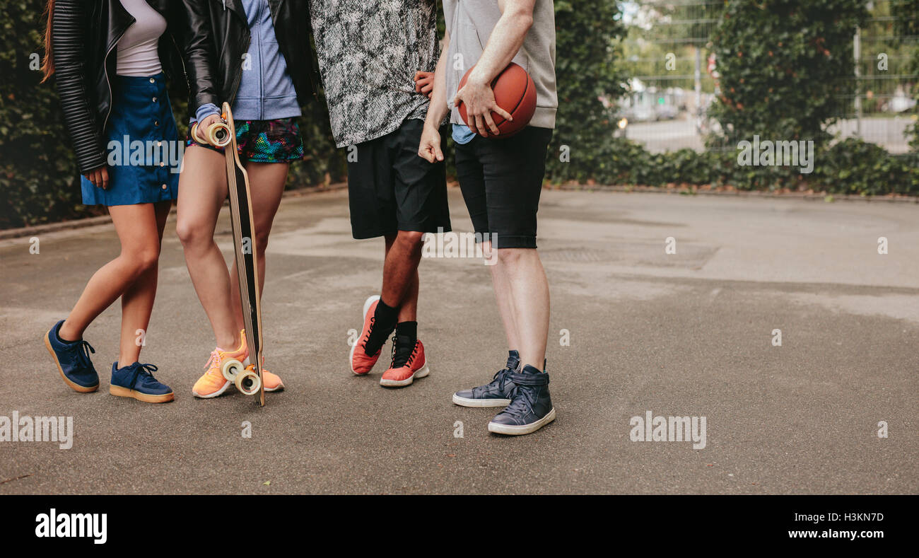 Cropped shot of group of people standing together with basketball and skateboard. Low angle shot with focus on men - Stock Image
