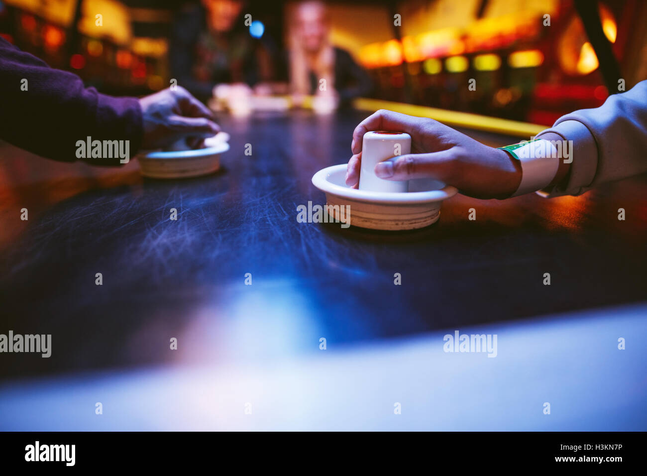 Hands of young people holding striker on air hockey table. Friends playing air hockey. - Stock Image