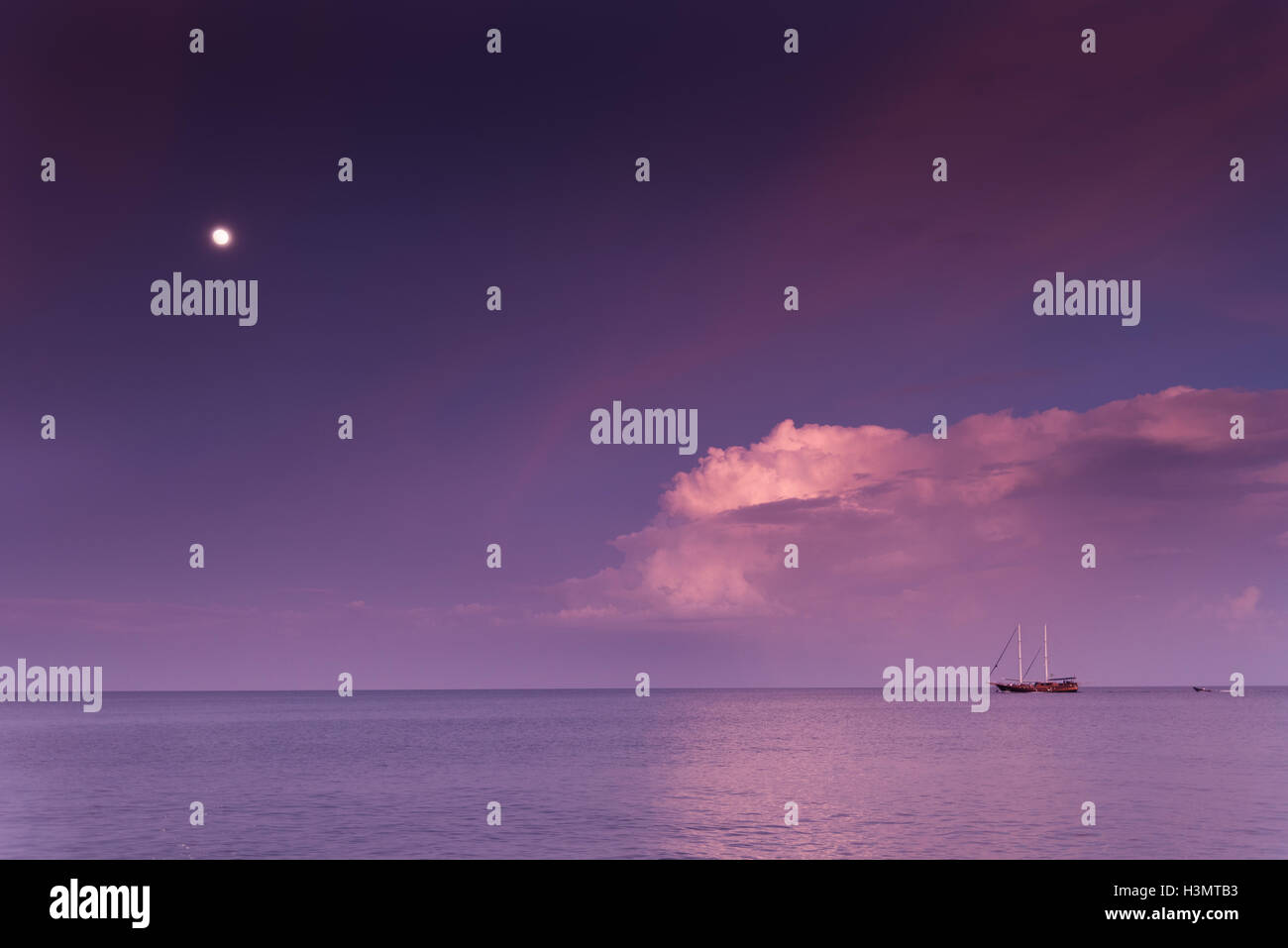 Sailing boat at the horizon during sunset - Stock Image