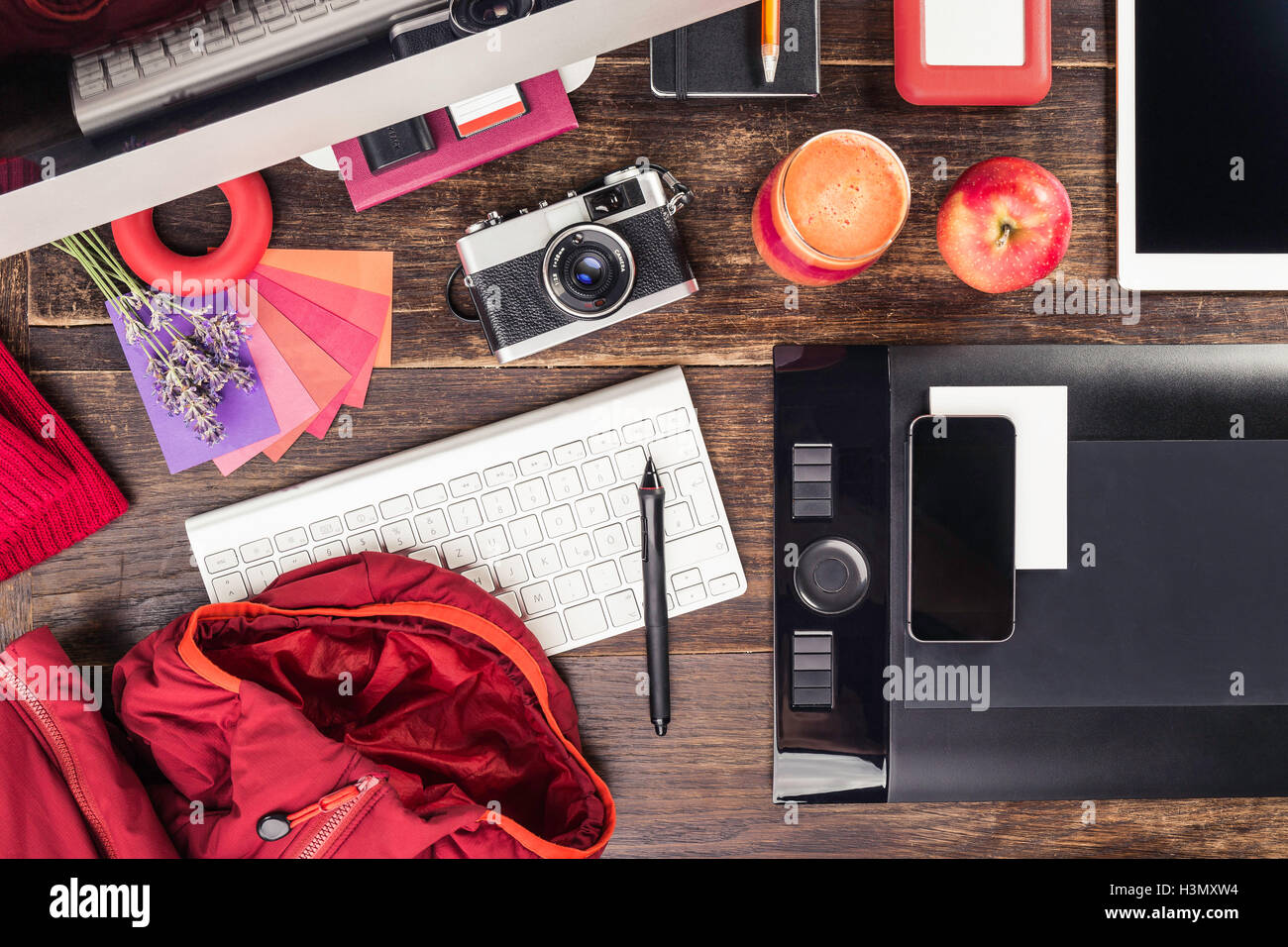 Overhead view of photo editing equipment; graphic tablet, digital tablet, retro camera, smartphone and desktop computer - Stock Image