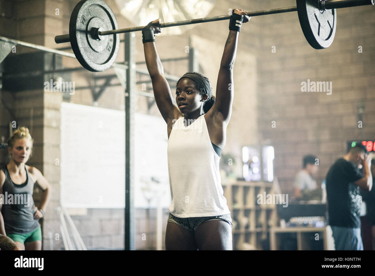 Cross training athlete lifting barbell in gym Stock Photo