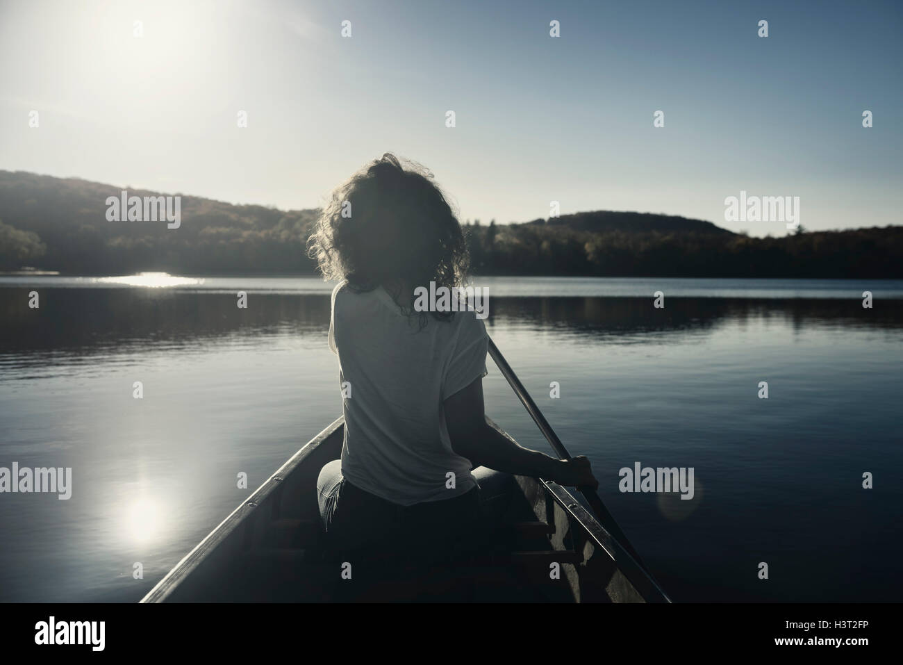 Young woman canoeing on a lake in fall. Muskoka, Ontario, Canada. - Stock Image