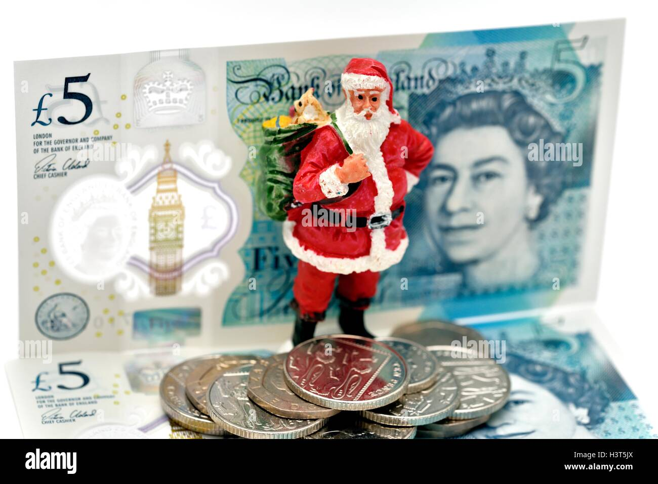 A santa claus figurine standing in front of some new five pound notes and coins.England UK. Stock Photo