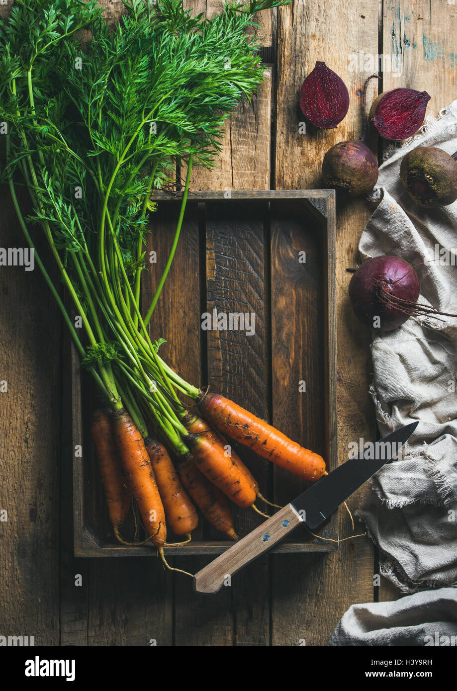 Garden carrots and beetroots in wooden tray over rustic background - Stock Image