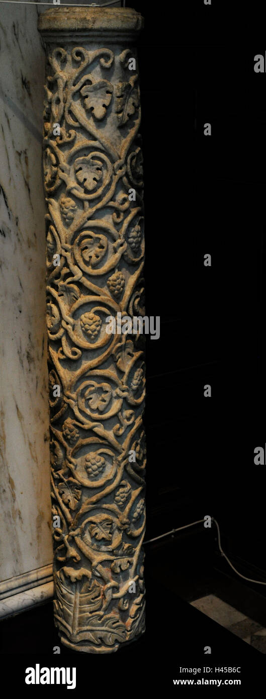 Embossed column decorated with acanthus leaves, vine tendrils and bunches of grapes. Remains of red polychrome. - Stock Image